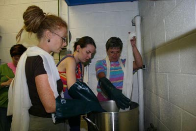 Vertical entry of silk fabrics into mordant pot to avoid air bubbles (Lisa Klakulak and participants, workshop at Appalachian Center for Craft, Smithville, TN, 2005)