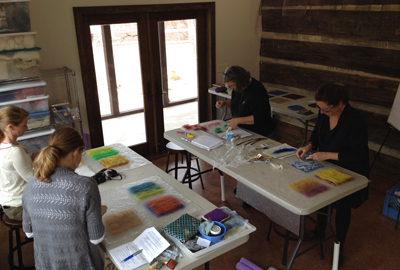 Participants laying out different types of fiber, different weights of fiber per area, exploring color blending and the incorporation of non-felting fibers (STRONGFELT STUDIO, 2014)
