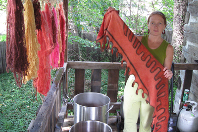 Lisa Klakulak revealing the differential take up of madder root dye on a silk fabric fused body textile as it is removed from the dye pot (STRONGFELT works, 2009)
