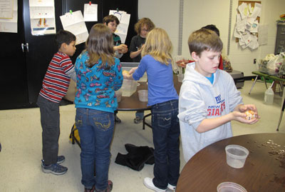 Students gently clasping their fiber covered balloons for the first dip in soapy water