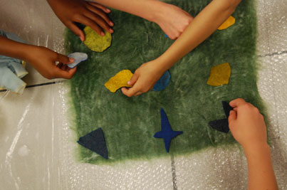Students considering the art principles of repetition, balance,  and focal point as they work together to place their partially felted positive shapes on the background